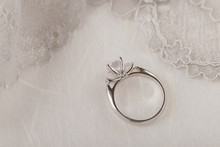 White Gold Wedding Ring With Diamonds On White Background With Lace