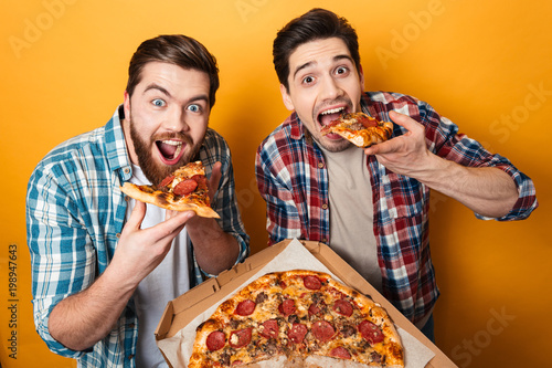 Portrait of a two hungry young men eating pizza Canvas Print
