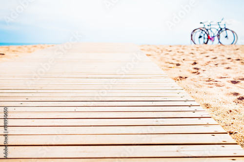 Fotografía  The end of the wooden road leading to the sea. Bicycle park.