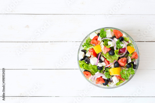 Fresh Greek salad in a bowl on wooden table, top view