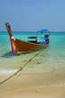Wooden boat on crystal clear shallow water, Koh Mai Phai island, Thailand