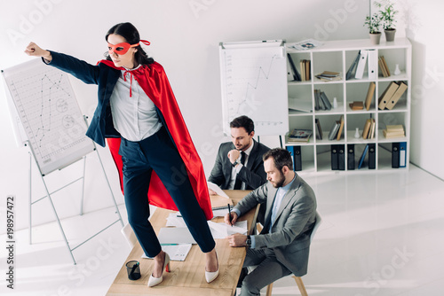 Photo  super businesswoman in mask and cape standing on table with hand up in office