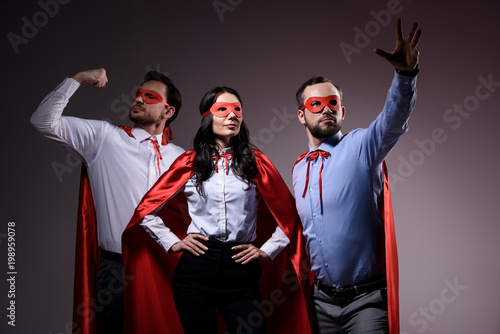 Photo  super businesspeople in masks and capes showing superpower isolated on grey