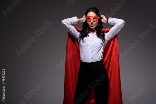 attractive super businesswoman in red cape tying mask isolated on black Wallpaper Mural