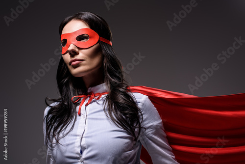 Fotografía attractive super businesswoman in red cape and mask isolated on black