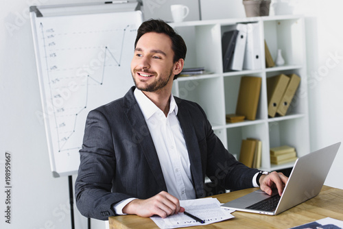 Garden Poster smiling handsome businessman sitting at table and looking away in office