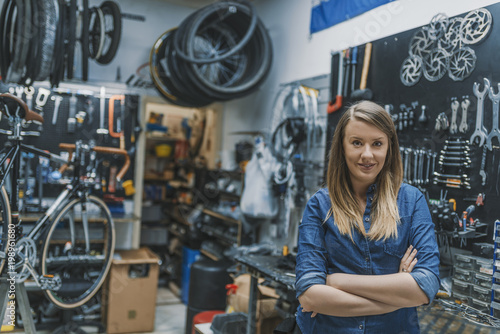 Portrait of young female mechanic in bicycle store