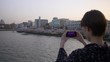 Beautiful woman taking photos of beautiful sakura from a bridge.