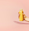 Leinwanddruck Bild - Summer beverages background with  yellow drink bottle in female hand at pastel pink background, front view. Creative minimal layout