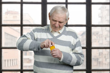 Very Old Senior Is Opening Bottle Of Pills. Twisting Cap Of Medicine Bottle. Checkered Windows Background.