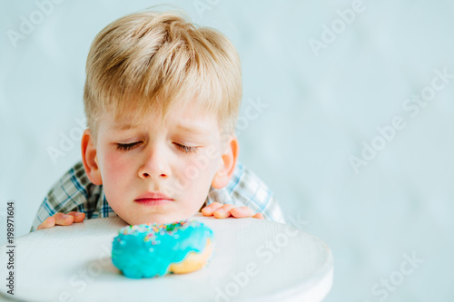 Платно Cute hungry baby boy looking on sweet donut