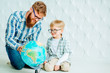 Beard caucasian father and his son in eyeglasses looking at globe over white polygonal wall background.