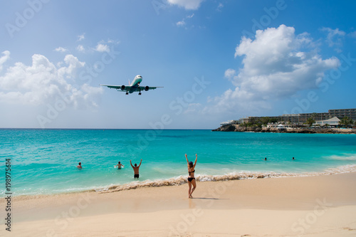 Foto auf AluDibond Karibik Plane land over people on beach of philipsburg, sint maarten. Jet flight low fly over blue sea. Airplane in cloudy blue sky. Beach vacation at Caribbean. Wanderlust, travel and trip