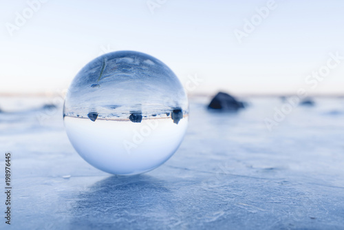 Black rocks in a glass orb on a frozen lake