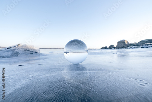 Elegant glass orb on ice on a frozen lake
