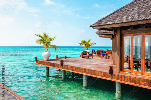 Fotografie, Obraz  A wooden restaurant on the water against the backdrop of the azure waters of the