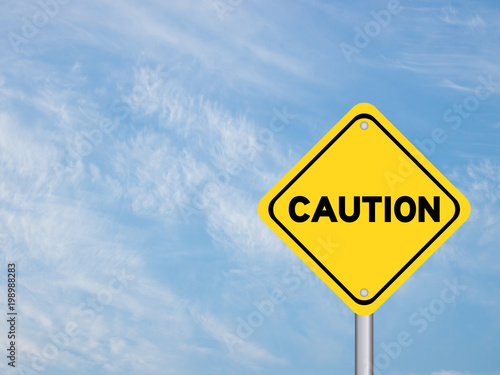 Fotografia Yellow transportation sign post with caution word on blue sky with cloud backgro