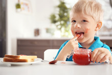 Cute Little Boy With Jar Of Jam At Home
