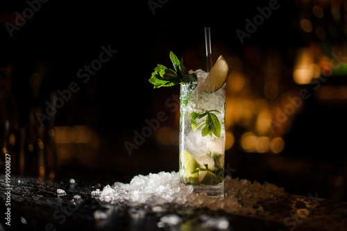Fototapeta alcoholic cocktail mojito stands on a bar counter