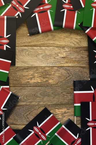 Fotografie, Obraz  Kenya small flags framing a wood texture background with copy space