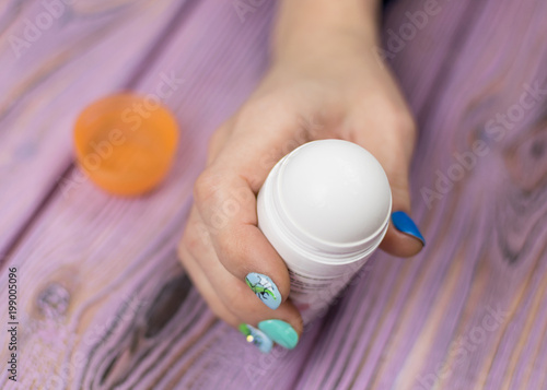 Photo Female deodorant in hand on a wooden background.