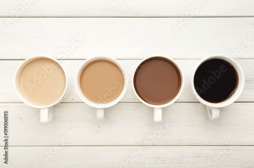 Various coffee cups on white wood, top view