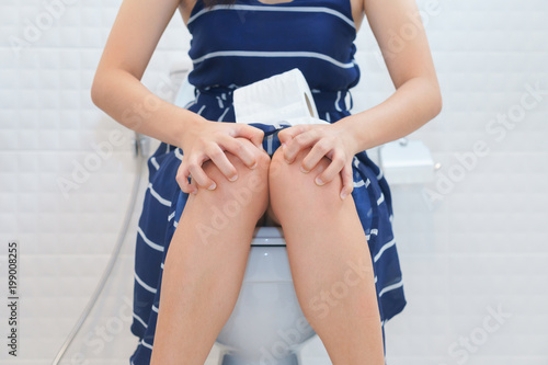 Cuadros en Lienzo Woman sitting on toilet with toilet paper - constipation concept