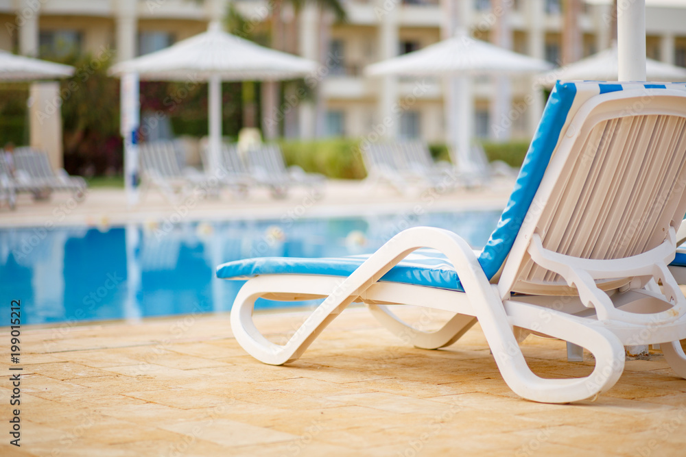 Fototapeta Chaise longue at the swimming pool in tropical resort. Tropical vacation concept background