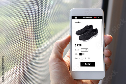 Hand holding mobile ecommerce website with black sneakers page in train