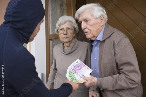 Fotografija Enkeltrick Seniorenpaar übergibt Geld