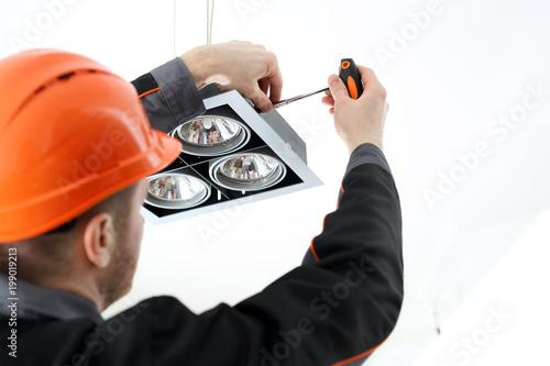 Obraz Fachowiec montuje oświetlenie. - fototapety do salonu