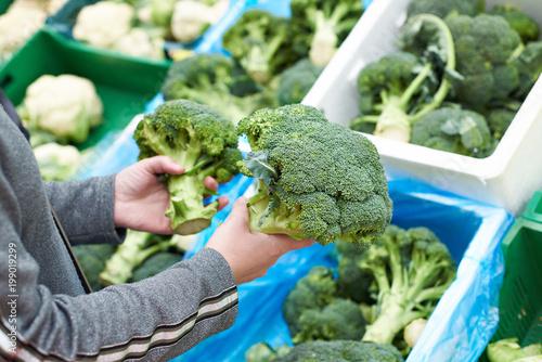 Plakat Kobieta kupuje brokuły w sklepie