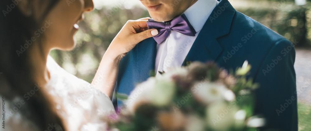 Fototapety, obrazy: Close-up image Bride Adjusting Groom's Tie, sun backlit. Bride put hand on groom's shoulder. Artwork