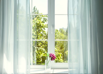 Window with curtains and flowers