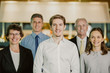 Closeup of business team of five serious diverse people standing and looking at camera with blurred interior in background. Two blurred businessmen are in background. Front view.