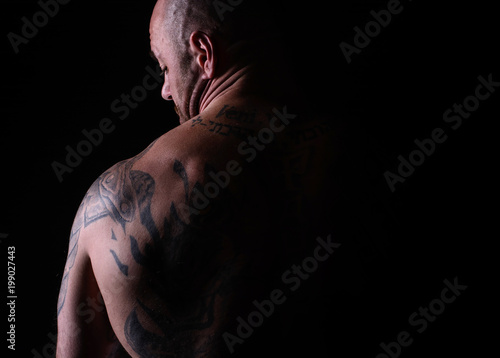 Fotografie, Tablou Muscle brutal athlete with tattoos posing in the studio and performing physical