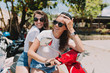 Two young beautiful hipster women riding on motorbike, summer island vacation, traveling, smiling, happy, having fun, sunglasses, stylish outfit, adventures, positive, friends together
