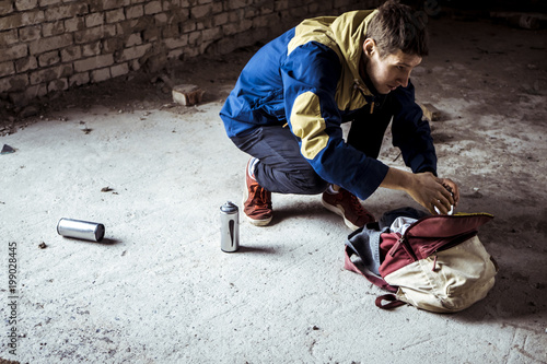 street artist taking spray paint cans near the wall in the abandoned building Poster