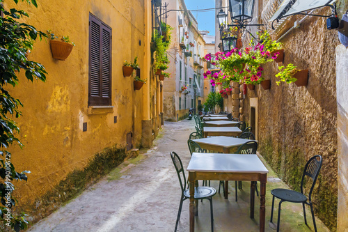 Cafe tables and chairs outside in old cozy street in the Positano town, Italy - 199030672