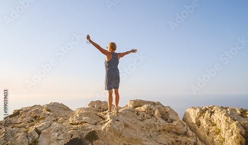 Fotografie, Obraz  Happy middle-aged woman in blue dress greets the sun dawn and enjoying life summ