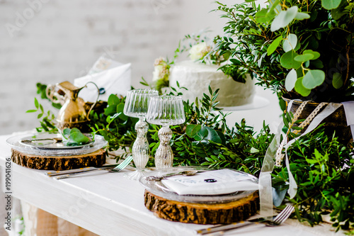 Holiday table with greenery and cutlery.