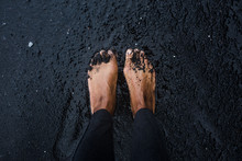 African American Feet Covered With Black Sand At The Beach