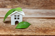 canvas print picture - Miniature white toy model house with green leaves on wooden backgdrop. Eco Village, abstract environmental background. Real estate mortgage property insurance dream home ecology concept