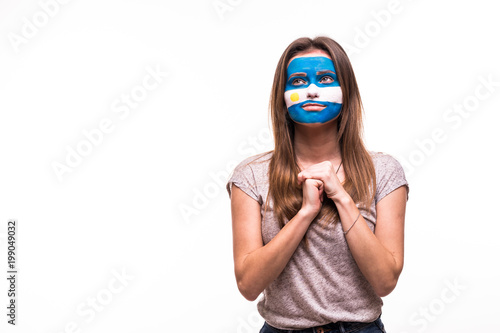 Fotografía Fan support of Argentina national team pray with painted face isolated on white