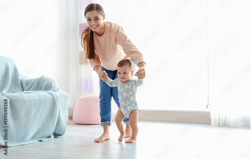 Fototapeta Baby taking first steps with mother's help at home