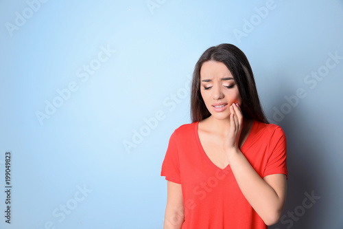 Fotografia  Woman with sensitive teeth on color background