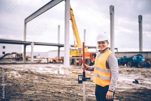Fotografie, Obraz  Surveyor engineer smiling with surveying tools and equipment at construction sit