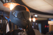 Black fashion carbon motorcycle helmet with orange insets on the shelf in the shop
