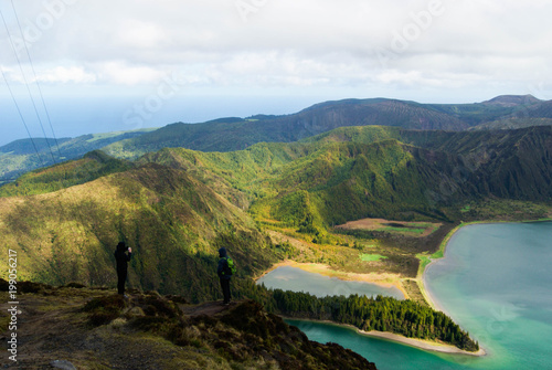 A couple of travellers on a top of Lagoa do Fogo in San Miguel island, Azores, Portugal.