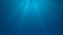 Calm Underwater Light Rays. Abstract Light Rays Of Sunshine Through A Soft Blue Background With A Tranquil Feeling Of Being Under Water Near The Surface.